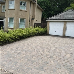 Sand is swept into all joints before sealant is applied to driveway.