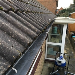 Gutter filled with leaves, moss and rainwater cleared, Ipswich, Suffolk